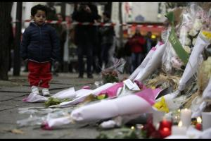 A child looks at the flowers and candles left along a rail cordon close to the Bataclan theatre in the 11th district of Paris on November 14, 2015, the day after a series of attack on the city resulting in the deaths of more than 128 individuals. Some 80 people were gunned down at the Bataclan theatre in Paris late November 13, during a concert by the US band Eagles of Death Metal. AFP PHOTO / KENZO TRIBOUILLARD